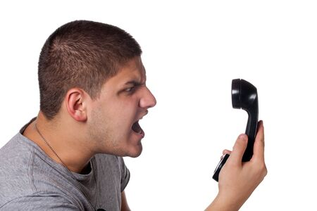 An angry and irritated young man yells into the telephone receiver over a white background. Stock Photo - 8908466