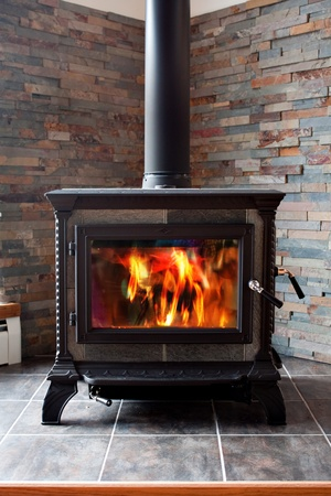 A new cast iron wood stove burning hot with slate tile. Stockfoto