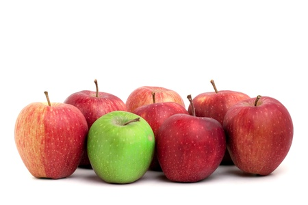 individuality: A lone green granny smith apple sits amongst a crowd of red delicious apples. Stock Photo
