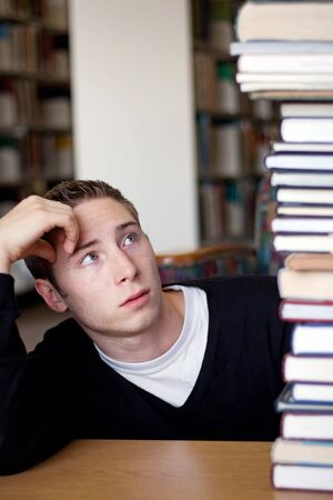 A frustrated and stressed out student looks up at the high pile of textbooks he has to go through to do his homework. photo