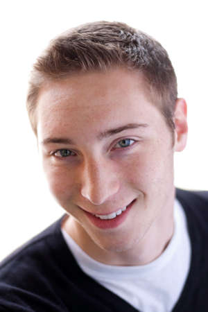 early twenties: High key portrait of a smiling young man in his early twenties. Shallow depth of field. Stock Photo