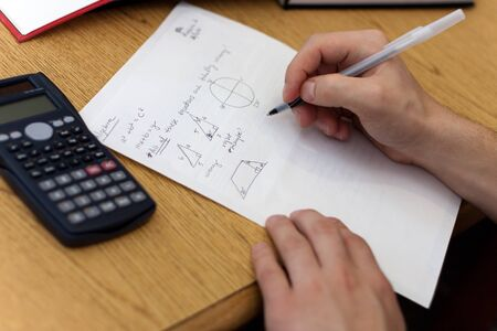 A young man working out mathematical equations on paper. photo