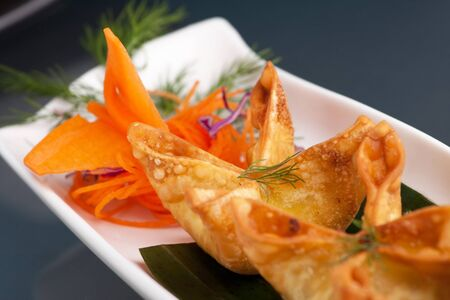 Fried thai crab cream cheese wontons or rangoons appetizer presented on a platter with fancy carrot and herb garnish. Imagens