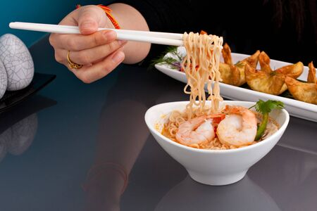 A person eating shrimp and Thai noodles from a bowl with chopsticks along with other appetizer foods. Stock Photo - 8908460