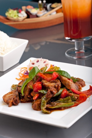 A fresh dish of Thai style roast chile basil duck with mixed vegetables white jasmine sticky rice and thai iced tea. photo