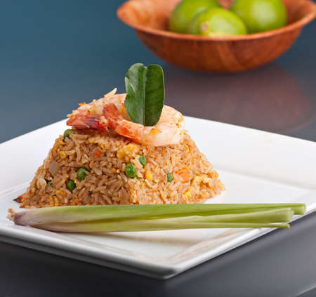 fried shrimp: A Thai dish of shrimp fried rice presented on a square white plate in the shape of a pyramid.