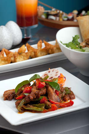 A fresh assortment of Thai style cuisine with a dish of chile basil duck with mixed vegetables thai iced tea and other appetizers. photo