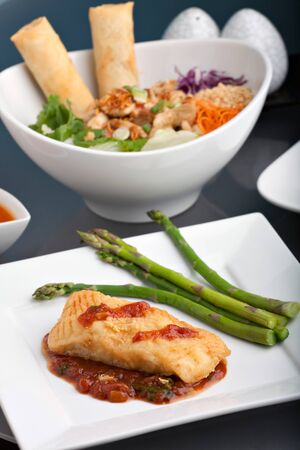 Freshly prepared Thai style sea bass fish dinner with asparagus and appetizer with a contemporary presentation. Imagens