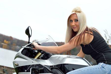 moteros: Una joven rubia plantea en su motocicleta.