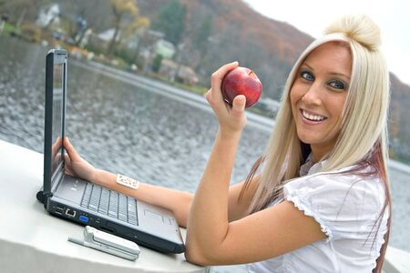 A beautiful young blonde woman in a mobile business setting eating a red apple while using her laptop notebook computer. Stock Photo - 8908462