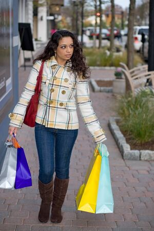 A young Indian woman carrying colorful bags out shopping in the city. Stock Photo - 8908409