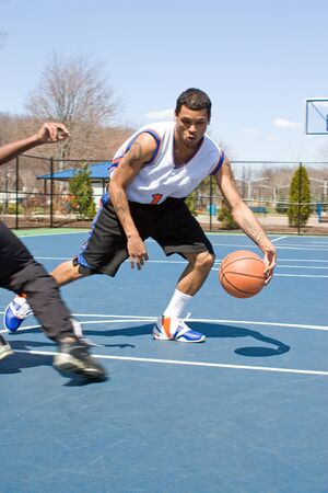 outdoor basketball court: A young basketball player dribbling the ball past the competition.