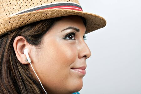 An attractive Hispanic woman listening to music playing through her stereo earbud headphones.  photo