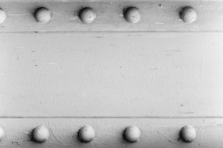 heavy duty: A silver painted metal background texture with four rusted bolts or rivets. Stock Photo