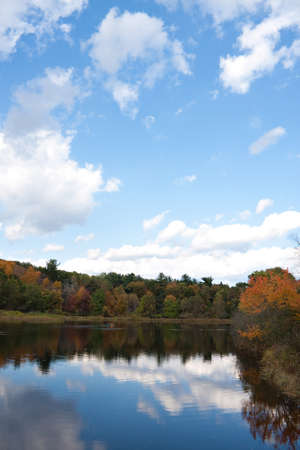 A gorgeous autumn scene with a lake and trees showing the bright colors of fall in New England. Kayakers enjoy the day in the distance. photo