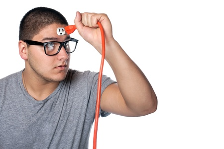 drained: Conceptual image of a young man holding an electrical chord disconnected from the outlet on his forehead.
