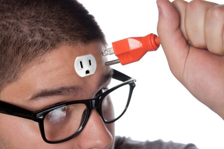 Conceptual image of a young man holding an electrical chord unplugged from the outlet on his forehead. photo