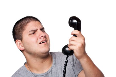 unsatisfied: An angry and irritated young man yells into the telephone receiver over a white background.
