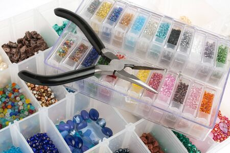 craft materials: An organizer full of multi colored beads and tools for making jewelry and crafts.