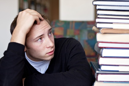A frustrated and stressed out student looks up at the high pile of textbooks he has to go through to do his homework. Stock Photo - 9019183