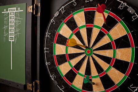 A professional dart board enclosed in a cabinet with slate chalkboard score boards. photo