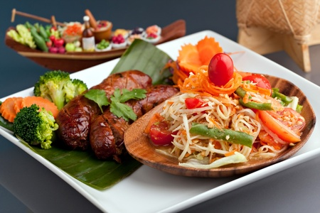 A dish of freshly prepared Thai sausage and som tum green papaya salad.