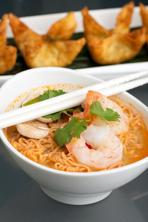 Shrimp and Thai noodle soup bowl with chopsticks along with fried wonton or rangoon type appetizers. photo