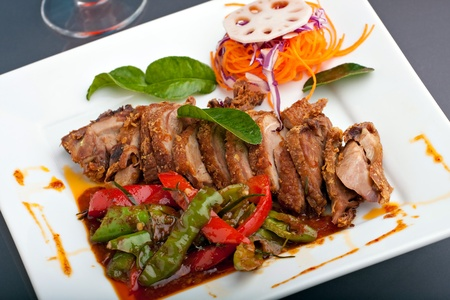 A fresh dish of Thai style roast chile basil duck with mixed vegetables garnished skillfully on a square white plate.