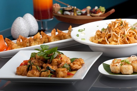 international food: A big assortment of Thai foods and appetizers presented beautifully with fancy garnish. Stock Photo