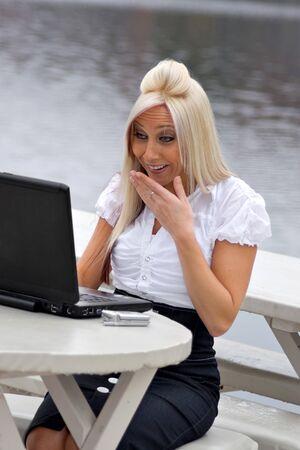 pornografia: Una joven y bella mujer rubia est� sorprendida por lo que est� viendo en la pantalla de su ordenador port�til.  Parece como si ella posiblemente est� viendo algo ofensivo.