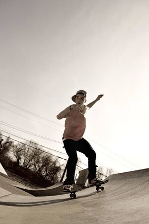 A young man skateboarding down a ramp at the skate park in sepia tone. photo