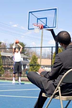 pfadfinderin: Ein Basketball-Trainer in einem Business-Anzug beobachten ein Spieler im Team.   Er k�nnte auch sein, Recruiter versucht, ihn scout.