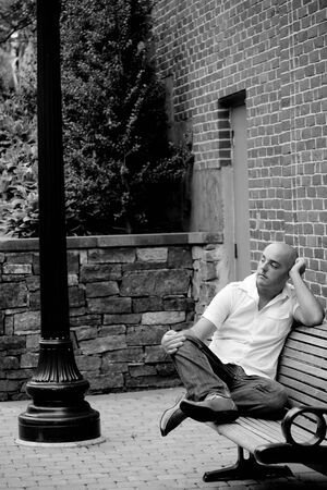 lamp post: A man in his twenties sitting casually on a bench in an urban area.