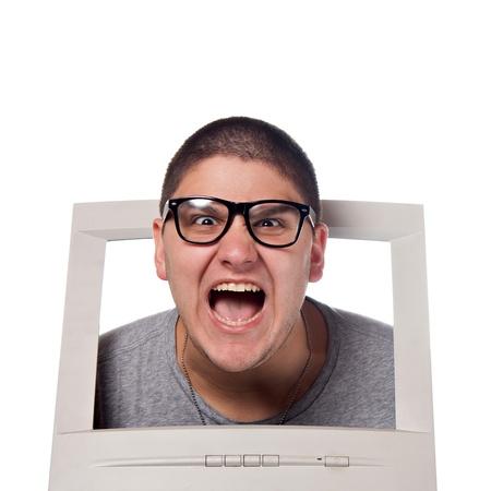 Een jonge man popping zijn hoofd uit voor een computermonitor met nerd bril.