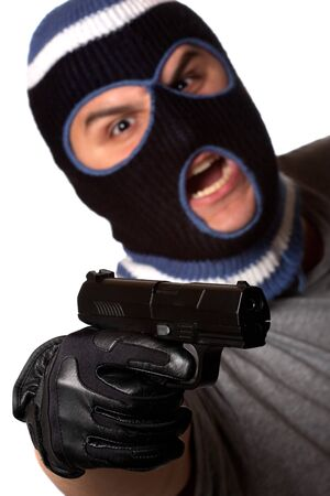 An angry looking man wearing a ski mask pointing a black handgun at the viewer. Shallow depth of field with sharpest focus on the gun. photo
