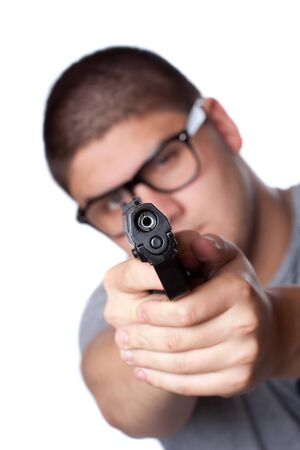 An angry looking teenager wearing glasses pointing a black handgun at the viewer. Shallow depth of field. photo