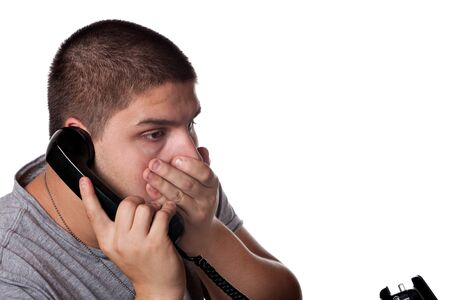 A young man on the phone places his hand on his mouth in disbelief of the news he has just heard. Stock Photo