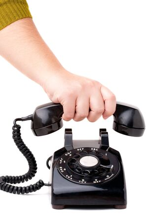 A hand  hanging up the handset of an old black vintage rotary style telephone isolated over white. photo