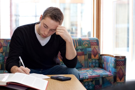 revising: A young college student cramming before his final exams. Stock Photo