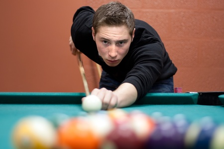 pool game: A young man lines up his shot as he breaks the balls for the start of a game of billiards. Shallow depth of field. Stock Photo
