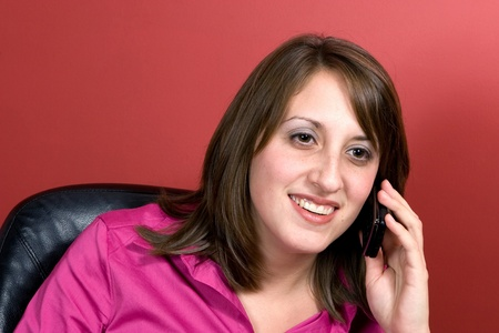 A young business woman talks on her cell phone isolated over a red background. photo
