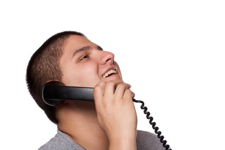 conversating: A young man listens on the telephone with a huge happy smile on his face.