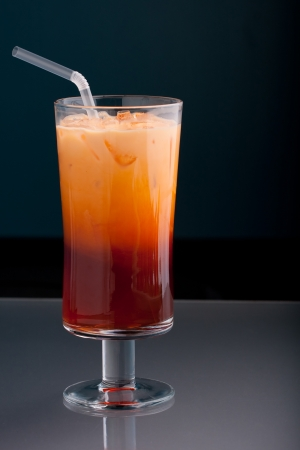 Thai iced tea served in a tall glass with cream and a straw. photo