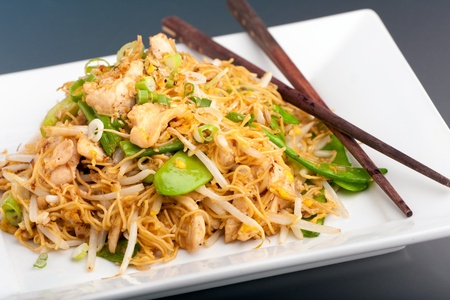 rice noodles: A Thai dish of chicken and noodles stir fry presented on a square white plate with wooden chopsticks.