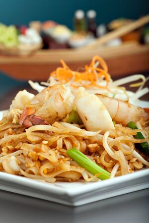 field of thai: Seafood pad Thai dish of fried rice noodles on a square white plate with chopsticks and grated carrot garnish. Shallow depth of field.