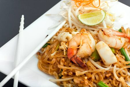 thai noodle: Seafood pad Thai dish of fried rice noodles on a square white plate with chopsticks and grated carrot garnish. Stock Photo