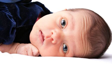 A cute newborn baby girl laying on a white backdrop. photo