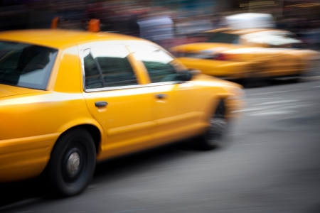taxicab: Abstract motion blur of a city street scene with a yellow taxi cabs speeding by.