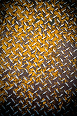 rust': Close up of real diamond plate material with a slight vignette.  Most of the yellow paint is chipped and scratched off.