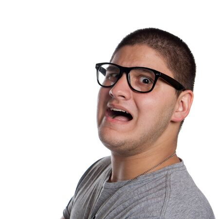 A goofy man wearing trendy nerd glasses isolated over white with a funny scared expression on his face. Stock Photo